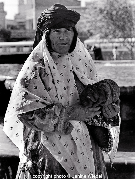 Nomadic tribal Qashqai woman in traditional dress on streets of Tehran Iran 1970s