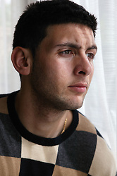 Portrait of a young man by a window; model released for use in HIV and Aids,