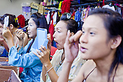 """Oct. 7, 2009 -- BANGKOK, THAILAND:  Ladyboys put their makeup on backstage at the Mambo Cabaret in Bangkok. The performers at the Mambo Cabaret in Bangkok, Thailand are all """"Ladyboys,"""" or kathoeys in Thai. Recognized as a third gender, between male and female, they are born biologically male but live their lives as women. Many kathoey realize they are third gender in their early teens, some only as old 12 or 13. Kathoeys frequently undergo gender reassignment surgery to become women. Being a kathoey in Thailand does not carry the same negative connotation that being a transgendered person in the West does. A number of prominent Thai entertainers are kathoeys. Photo by Jack Kurtz / ZUMA Press"""