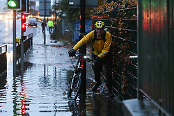 © Licensed to London News Pictures. 22/11/2016. Rotherham, UK. A cyclist walks through a flooded road in Rotherham, South Yorkshire, after a river broke it's banks last night. Storm Angus has brought heavy wind and rain to much of the UK this week with flooding seen all over. Photo credit : Ian Hinchliffe/LNP