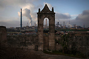 """The Arcelor Mittal steel works factory dominates the skyline from an old abandoned """"masseria"""", an Italian fortified farmhouse on a country estate, in Taranto, southern Italy, March 9, 2019. During days of strong winds, local authorities close schools as the air fills with toxic dust from heavy metals. Children are told to stay indoor. In 2010, the local council prohibited children to play in certain residential areas of the city, because of soil contaminated high above safety levels."""
