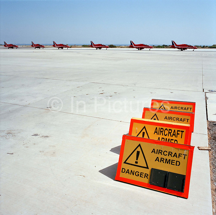 BAE System Hawks of the Red Arrows, Britain's RAF aerobatic team and airfield signs landscape. Six Hawk jet aircraft of the elite team, taxi in after another training flight past warning boards that are appropriate for armed jet fighters at RAF Akrotiri, Cyprus rather than aerobatic planes. From a low angle we see a wide landscape looking over the taxi-way markings that direct military airplanes. The Red Arrows aircraft are a deep red colour that stand out against the horizon in an identical line. It is a wide expanse of road surface, the yellow centre-lines are for the benefit of pilots who need guidance for parking areas after landing, or leaving towards the departing runway on the southern part of the Cypriot Mediterranean island. With the Red Arrows, the  taxiing jets all peel off in unison to and from the parking area and these lines are vital for this technique.