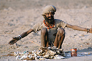 Indian man outside Delhi with rags he has collected, India