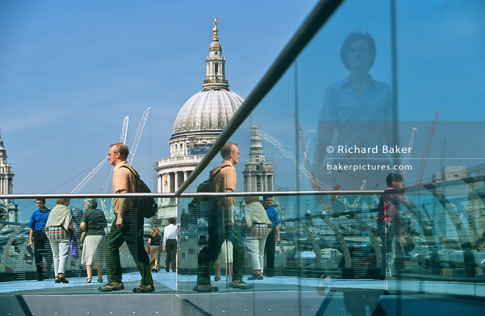 Pedestrians walk over the Millennium Bridge with St Pauls Cathedral in the background over the River Thames, London.