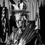 Lipan Apache Tribe of Texas' Robert Soto battled with the United States federal court over his right to keep and wear eagle feathers for nine years. His feathers were returned to him in 2015, but he hopes his small tribe will be federally recognized now that they has a judgment in their favor. Soto is seen wearing two of his eagle feathers atop his head. (4X5 Ilford HP5) photo by Nathan Lambrecht