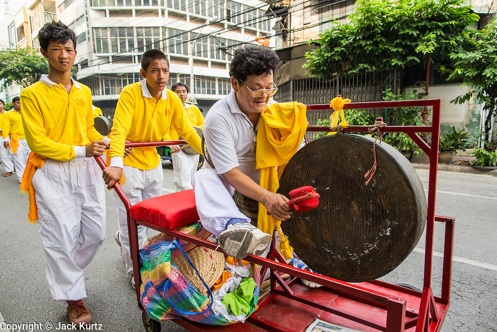 14 OCTOBER 2012 - BANGKOK, THAILAND:  Men play gongs during a procession on the first day of the Vegetarian Festival in Bangkok's Chinatown. The Vegetarian Festival is celebrated throughout Thailand. It is the Thai version of the The Nine Emperor Gods Festival, a nine-day Taoist celebration beginning on the eve of 9th lunar month of the Chinese calendar. During a period of nine days, those who are participating in the festival dress all in white and abstain from eating meat, poultry, seafood, and dairy products. Vendors and proprietors of restaurants indicate that vegetarian food is for sale by putting a yellow flag out with Thai characters for meatless written on it in red.     PHOTO BY JACK KURTZ