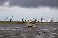 """A  fishing boat owned by members of  Pointe-aux-Chien Indian living in Pointe aux Chene being used  as a """"vessel of opportunity""""  to put boom out for BP returning to port after a rain storm.  Crab and shrimp season were officially closed on May 29th, 2010, due  to the BP oil spill that is making its' way into the lakes and bayous close to Pointe-au-Chien."""