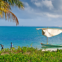 Workers hand pull a dow sailboat along the shore.  Island beach resort just off the coast of Mozambique.  Benguerra Lodge.