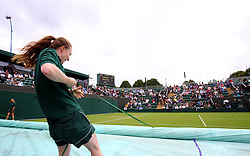 Ground staff remove the covers from court three after a rain break on day one of the Wimbledon Championships at The All England Lawn Tennis and Croquet Club, Wimbledon.
