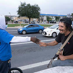 Musician and handyman Douglas Crawford, r, greets a street boddy as he strums his guitar for spare change near his camp at the corner of Ben White Blvd. and south Congress Avenue in Austin, TX where he's lived for over a year. Crawford, 60, says he stays to himself and isn't worried about Austin's new homeless crackdown and camping ban starting Tuesday.