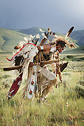 Traditional Shoshone dancer photographed in Wyoming in full costume. Golden eagle feathers embellish the dance gear, bustle and headdress against stone cliffs and rolling hills.
