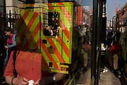 Reflections of Londoners and the reflected rear of an National Health Service (NHS) London ambulance stopped near a bus shelter. It is a busy pavement outside the main entrance to the Royal Academy (RA) art museum and gallery on the capital's Piccadilly in London's west end. The ambulance has been called to a visitor who has fallen ill inside the RA and its presence within the frame of the shelter makes for a confusing landscape. Various people's faces and bodies mix with the high-visibility stripes of the vehicle's rear doors.