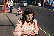 Elderly woman smoking a cigarette in Paddington, London, England, United Kingdom.