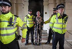 © Licensed to London News Pictures. 07/10/2019. London, UK. An Extinction Rebellion protestor with a painted face being arrested by police at Horseguards in Westminster. Activists will converge on Westminster blockading roads in the area for at least two weeks calling on government departments to 'Tell the Truth' about what they are doing to tackle the Emergency. Photo credit: Ben Cawthra/LNP