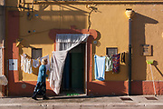 An old woman put some cloths to dry in the village of Poggiorsini, Italy. Poggiorsini was a feud of the Orsini family who gave their name to the country. It is the smallest city center in the metropolitan city of Bari and is part of the National Park of the High Murgia of Apulia region.