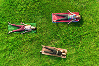 Aerial view of three women doing yoga on grass in the park.