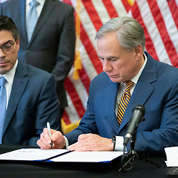 Texas Gov. Greg Abbott (c) with legislators and energy officials, signs two bills strengthening the Texas power grid and infrastructure that were emergency items on his legislative agenda. The bills were in response to February's winter storm that nearly knocked out the Texas power grid.  At left is Rep. Chris Paddie, R-Marshall.