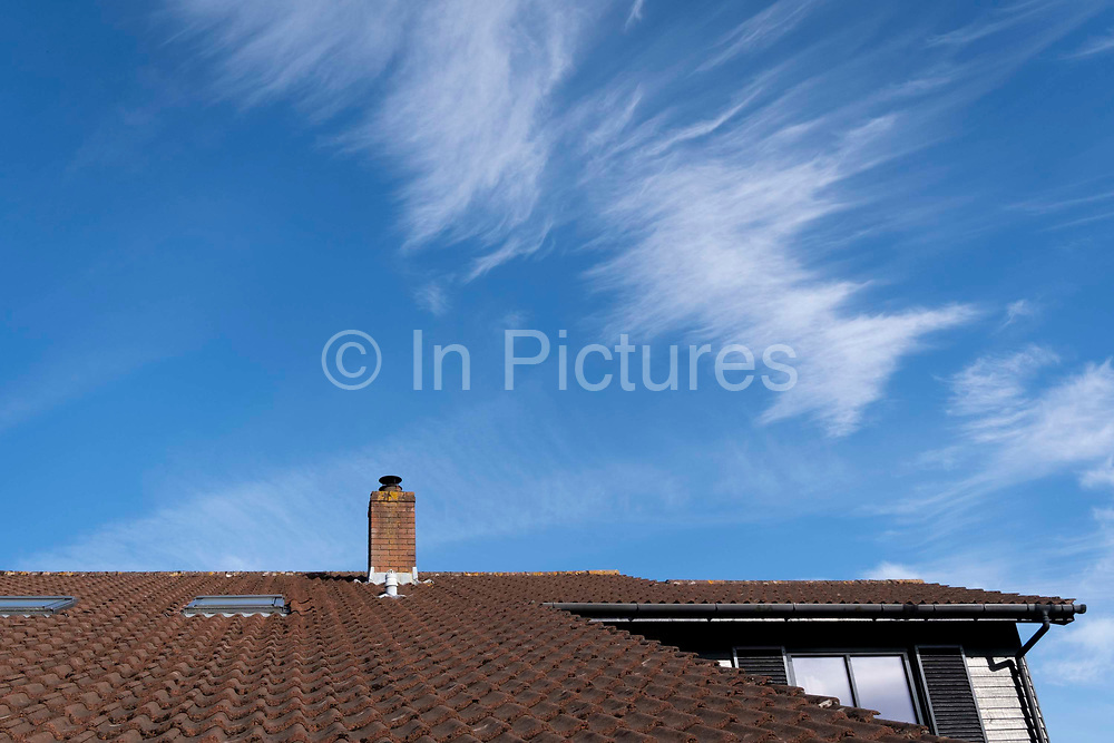 High-altitude cirrus cloud above the chimney and sloping roof of an English suburban house, on 30th May 2021, in Nailsea, North Somerset, England.