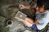 Top view of Laotian man making a metal flower design in the 'Spoon Village'<br />  (Ban Napia), Phonsavan, Xieng Khouang Province, Laos, Southeast Asia. Since the late 1980's the people of this village have created spoons using aluminium UXO scraps left from the Indochina War.