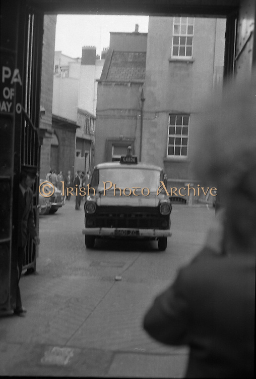 Fergus Rowan sits in at Bank of Ireland.  (J70)..1975..22.08.1975..08.22.1975..22nd August 1975..As a result of the 1970 bank strike which lasted for six months, the Rowan family business found itself in financial difficulties. During the strike the Rowans had had to accept cheques in good faith in order to stay in business. When the cheques came for settlement the bank refused as they stated that some were 'dodgy'. This put severe strain on the business which was eventually put into receivership.As part of the process the Rowan business beside the bank was put up for sale and was purchased by B.o I. Rowan was outraged and started a campaign against the bank which culminated in a sit in at the banks headquarters in Westmoreland St,Dublin. He also became a thorn in the side of the bank at the A.G.Ms raising many points...Picture shows the Garda van, containing Mr Rowan, leaving the back of the bank after his removal from the premises.