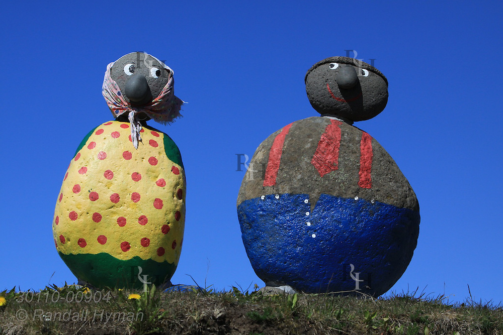 Whimsical statues of farm couple made of painted boulders stand at Highway 1 road crossing leading to town of Hvammstangi, Iceland.