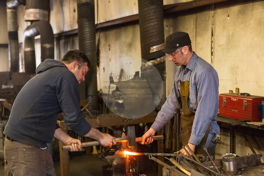Blacksmiths forge a red hot piece of steel using hammers and anvil in a metal working shop in Charleston, SC
