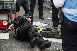 London, UK. 6 September, 2019. Metropolitan Police officers arrest an activist who had locked herself beneath a truck making a delivery to ExCel London for DSEI, the world's largest arms fair. The road remained blocked for several hours. The fifth day of protests against the arms fair was themed as Stop The Arms Fair: Stop Climate Change in order to highlight links between the fossil fuel and arms industries.