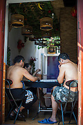 Chinese men play typical Chinese chess called mahjong under their birds' bamboo cages in a courtyard of a hutong in Beijing, China, August 15, 2014.<br /> <br /> Food and games are a real pleasure for the life of Chinese community. <br /> At home, in the streets, at the park or in restaurants, the chance to find someone eating or playing is considerably high.<br /> <br /> © Giorgio Perottino