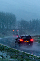 © Licensed to London News Pictures. 13/01/2016. Brecon, Powys, Wales, UK. Traffic negotiates the A470 road over the Brecon Beacons near the Storey Arms during a blizzard of sleet and snow. Photo credit: Graham M. Lawrence/LNP