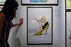 """© Licensed to London News Pictures. 31/03/2017. London, UK. A staff member views """"Sod Off"""" by Gerald Scarfe (Est. GBP 2-3k), a caricature of Theresa May.  Press preview of """"Made in Britain"""" at Sotheby's in New Bond Street.  The auction on 5 April celebrates innovative British art in the twentieth century as well as artwork by political cartoonist Gerald Scarfe. Photo credit : Stephen Chung/LNP"""