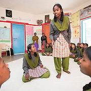CAPTION: Mahila Samakhya students act out a role-play. In the play, the old lady's granddaughter has just started menstruating. She is worrying about what's happening her, so goes to her grandmother and asks why this is suddenly happening to her. The old lady reassures her that it happens to every woman; that it also happened to her, and that there's nothing to worry about, everything will be alright. The girl who then comes along is playing the role of a sahiya. She is visiting the household, and reassures the girl that it's a natural process for all young girls, and goes on to explain how to take care of nutritional intake including supplementation during this period, and also how to be clean and hygienic. She then assures her that if she experiences very bad pain, she can come to her for some medicines. LOCATION: Mahila Samakhya, Ratu (block), Ranchi (city), Jharkhand (state), India. INDIVIDUAL(S) PHOTOGRAPHED: Foreground, from left to right: Salomi Horo, Shobha Pareya, Sita Kujur and Ganga Purti; background: multiple people.