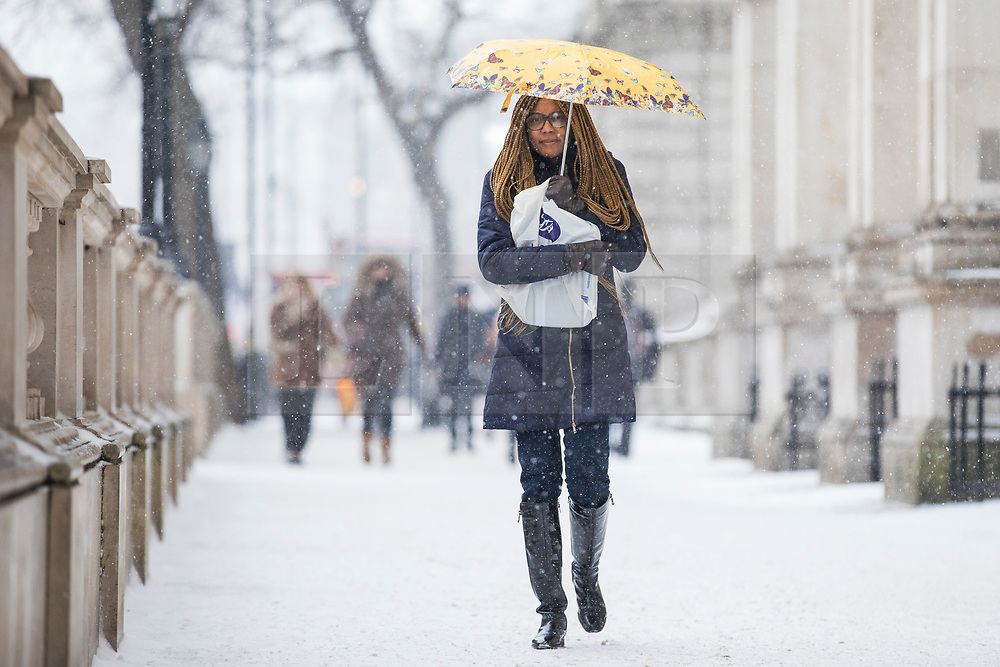© Licensed to London News Pictures. 01/03/2018. London, UK. A woman shelters beneath an umbrella as snow falls on Whitehall in London. The 'Beast from the East' and Storm Emma have brought extreme cold and heavy snow to the UK. Photo credit: Rob Pinney/LNP