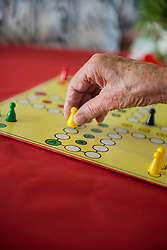 Close-up of senior woman playing ludo board game, Bavaria, Germany, Europe