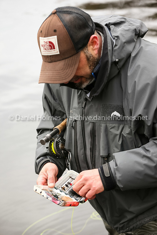 (3/26/16, ASHLAND, MA) Rich Soriano, of Hudson, selects a fly while trout fishing at Ashland Reservoir on Saturday. MassWildlife is stocking close to 500,000 trout in Massachusetts this Spring. Ashland Reservoir is one of the bodies of water that was recently stocked. To see others, you can go to http://www.mass.gov/eea/agencies/dfg/dfw/hunting-fishing-wildlife-watching/fishing/trout-stocking-schedule.html  Daily News and Wicked Local Photo/Dan Holmes