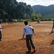 Hmong students in Vieng Xai in northeast Laos playing a traditional game of tujlub, which involves spinning wooden tops hurled with string and sticks. While one top is still spinning, another person tries to hit it. If they don't hit it, they're out. If they do hit it, the winner is the one whose top continues spinning the longest.