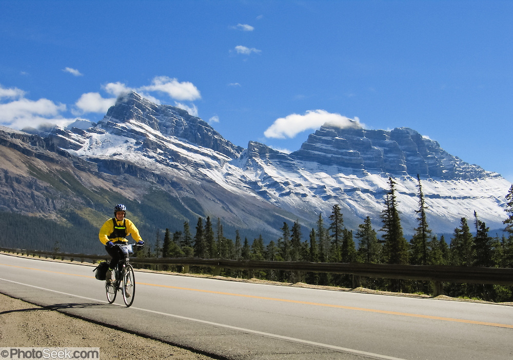 A bicyclist zooms down Icefields Parkway south of Sunwapta Pass in Banff National Park, Alberta, Canada. This is part of the big Canadian Rocky Mountain Parks World Heritage Site declared by UNESCO in 1984.