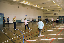 Group of older people playing badminton games in a sports hall,
