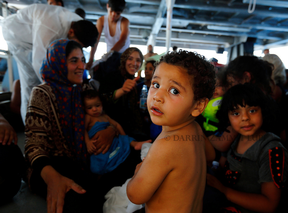 Migrants including children sit on the lower deck of the Migrant Offshore Aid Station (MOAS) ship MV Phoenix after being rescued from an overloaded wooden boat 10.5 miles off the coast of Libya August 6, 2015.  An estimated 600 migrants on the boat were rescued by the international non-governmental organisations Medecins san Frontiere (MSF) and MOAS without loss of life on Thursday afternoon, a day after more than 200 migrants are feared to have drowned in the latest Mediterranean boat tragedy after rescuers saved over 370 people from a capsized boat thought to be carrying 600.<br /> REUTERS/Darrin Zammit Lupi <br /> MALTA OUT. NO COMMERCIAL OR EDITORIAL SALES IN MALTA