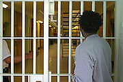 A prisoner waits to be let through an internal security gate buy a prison officer on D wing. HMP Wandsworth, London, United Kingdom