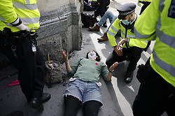© Licensed to London News Pictures. 02/09/2020. London, UK. Police stand over an Extinction Rebellion protester after he was removed from the road in Whitehall. A second day of protests is taking place in central London. Photo credit: Peter Macdiarmid/LNP