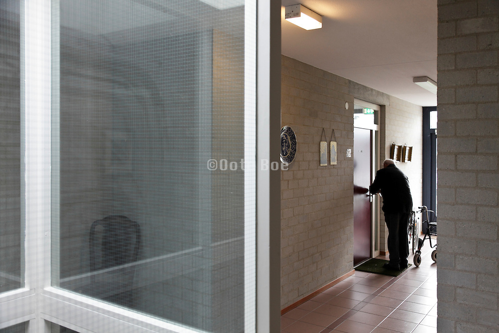 senior man at the door of his apartment in a independent living retirement home