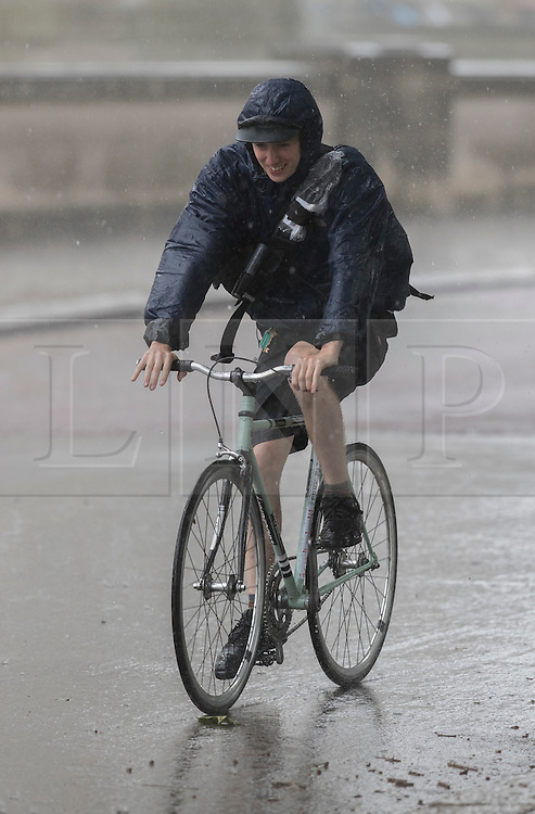 © Licensed to London News Pictures. 12/07/2016. London, UK. A cyclist gets a soaking as a sudden rain storm hits central London. Photo credit: Peter Macdiarmid/LNP