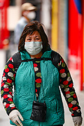 A woman wearing a face mask walks alongside the China Town near Leicester Square in central London on Monday, May 11, 2020. <br />