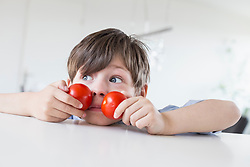 Boy making faces with tomatos