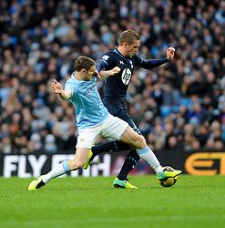 Tottenham Hotspur's Gylfi Sigurosson is challenged by Manchester City's James Milner - Photo mandatory by-line: Dougie Allward/JMP - Tel: Mobile: 07966 386802 24/11/2013 - SPORT - Football - Manchester - Etihad Stadium - Manchester City v Tottenham Hotspur - Barclays Premier League