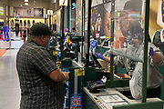 A customer makes a purchase at Dick's Sporting Goods store at the Los Cerritos Center mall amid the global coronavirus COVID-19 pandemic, Saturday, May 30, 2020, in Cerritos, Calif.