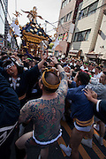 Tattooed men, some members of criminal gangs called Yakuza, help as Mikoshi are carried around the streets of Asakusa during the Sanja matsuri. Asakusa, Tokyo, Japan. Sunday May 15th 2016 The Sanja matsuri is one of the biggest festivals in Japan. Taking place over the 3 days of the second weekend of May (May 13th to 15th) it features many mikoshi, or portable shrines, that are carried around by local groups to bring blessings and prosperity to their neighbourhoods