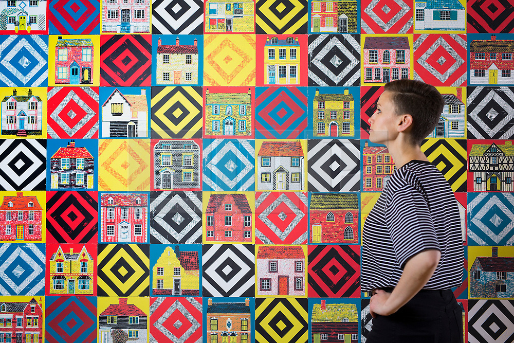 """© Licensed to London News Pictures. 15/06/2017. Wakefield UK. Picture shows Kerry Chase from the Yorkshire Sculpture park looking over a wall hanging screen printed """"quilt"""" by Illustrator Alice Pattullo. Alice Pattullo has a new exhibition at the Yorkshire Sculpture park called Of House & Home which is her most ambitious project to date & includes 60 new screen printed editions revealing Pattullo's fascination with traditions, superstitions & folklore. The exhibition takes visitors on a journey through a victorian household from garden to parlour culminating with the heart of the home a recreation of a traditional fireplace & mantlepiece. Photo credit: Andrew McCaren/LNP"""