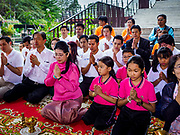 05 JANUARY 2019 - MINBURI, BANGKOK, THAILAND:  SUDARAT KEYURAPHAN (center left, pink blouse, pink skirt), the Pheu Thai Party candidate for Prime Minister of Thailand, and other supporters of the Pheu Thai Party pray before monks collected alms at the Kwan Riam Floating Market at Wat Bamphen Nuea in Minburi, east of downtown Bangkok. The Thai government has tentatively scheduled a general election for 24 February 2019. It will be Thailand's first election since a military coup overthrew the government of Yingluck Shinawatra in 2014. Yingluck was a the leader of the Pheu Thai Party before her ouster. Sudarat was a member of Thaksin Shinawatra's cabinet. Thaksin's government was also deposed by a coup in 2006.       PHOTO BY JACK KURTZ