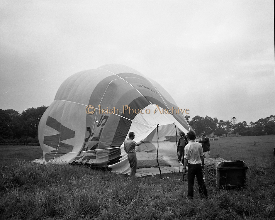 Dew Mighty Minerals Hot Air Balloon.   (H15)..1974..07.08.1974..08.07.1974..7th August 1974..The launching of the Dew Mighty Minerals hot air balloon,took place in Tullamore,Co Offaly last night,as part of the Tullamore Festival Week. The balloon was piloted by Mr Wilf Woollett,a veterinary surgeon from Loughrea,Co Galway and his co-pilot was Kevin Haugh. Miss Rosemary Mannion,the Offaly Rose of Tralee contestant sent the balloon on its way by popping a bottle of Champagne over it.  The balloon itself has a capacity of 56,000 cubic feet,is 60ft high and 50ft wide. It is made from nylon/polyproplene. The basket is 2ft square by 3ft high and carries two people,it is attached to the balloon by steel cables..Wilf Woollett has piloted the balloon in the U.S. and Britain and is a member of the Dublin Balloon Club...Picture shows the balloon being inflated.
